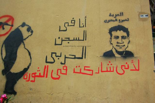 On the wall of a public bathroom on Abdel Salam Aref across from El Horreya, Sad Panda sits next to a graffiti stencil by Xist of Amr Beheiry, imprisoned Tahrir protester